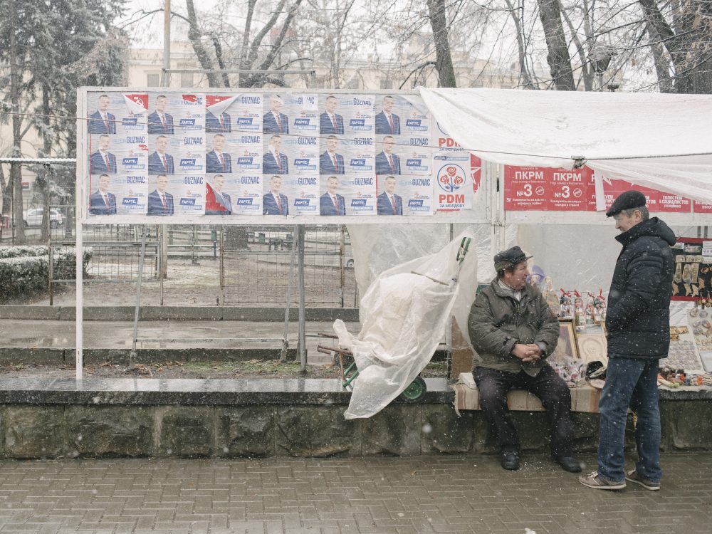 Election posters of Democratic Party and Communist party next to souvenir market in Chisinau. Republic of Moldova.